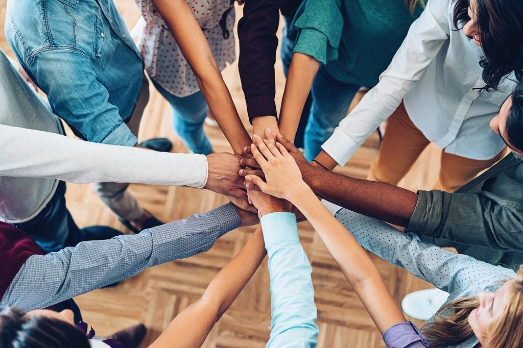 Gruppen hält Hände in die Mitte