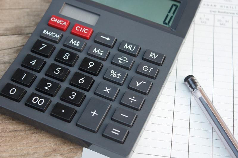 Taschenrechner mit Papier und Stift